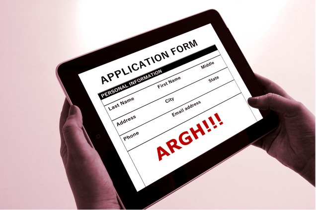 A frustrated person holding a tablet displaying an application form.